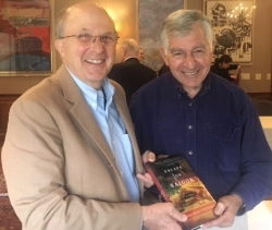 Novelist Dick Pirozzolo Presents a Copy of His