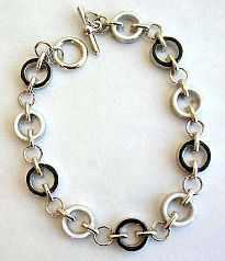 Fashion bracelet in multi enamel black and white circle pattern design, with toggle jewelry clasp fo
