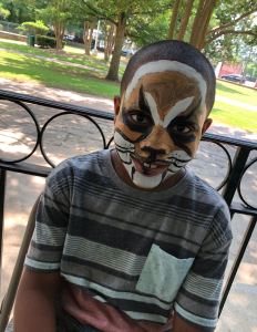 Participant in the Art in the Park program showing off his freshly painted tiger face